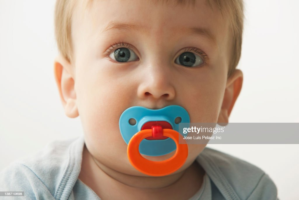 Mixed race baby boy sucking pacifier : Stock Photo