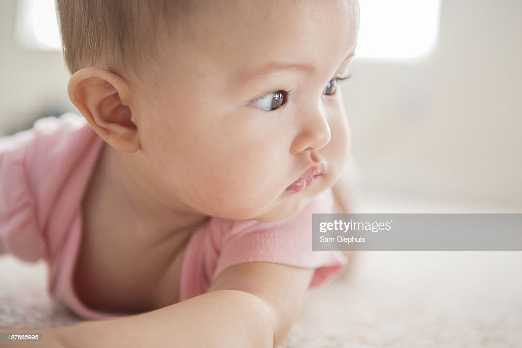Mixed race baby girl laying on carpet : Stock Photo