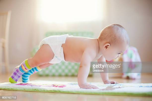 Mixed race baby girl playing on floor