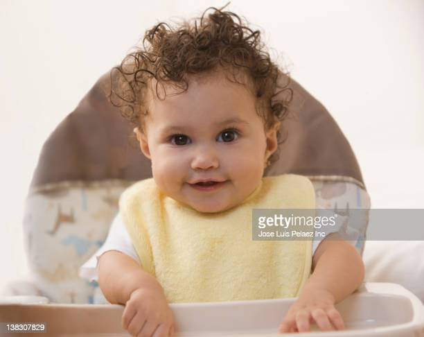 Mixed race baby girl sitting in highchair