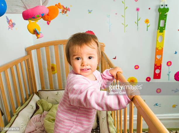 Mixed race baby girl standing in crib