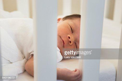 Mixed race baby sleeping in crib : Stock Photo
