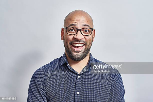 Mixed race bald British male looking surprised