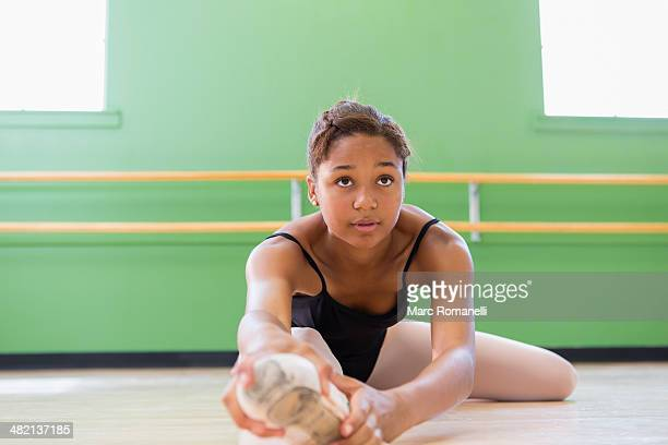 Mixed race ballerina stretching in studio
