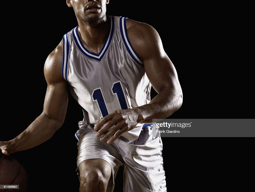 Mixed race basketball player bouncing basketball : Stock Photo
