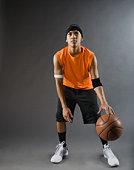Mixed race basketball player dribbling basketball
