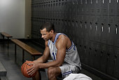 Mixed race basketball player sitting in locker room