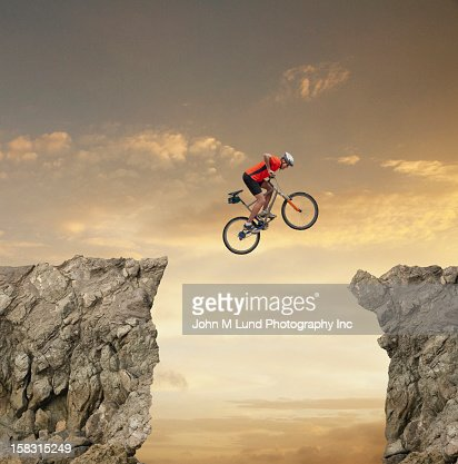 Mixed race bicyclist jumping over canyon