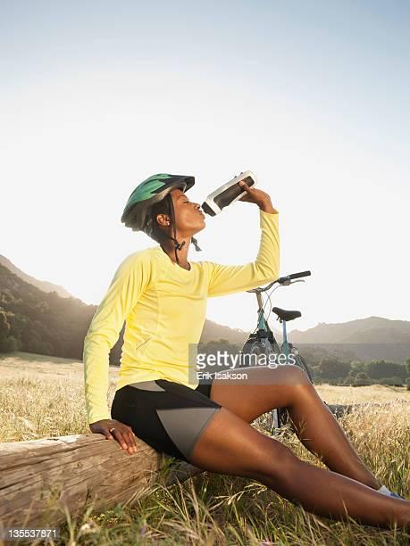 Mixed race biker taking a break and drinking water