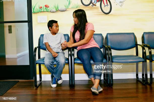Mixed race boy and mother in waiting room
