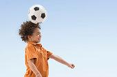 Mixed race boy balancing soccer ball on forehead