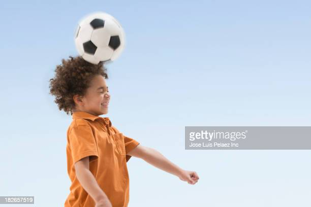 Mixed race boy balancing soccer ball on forehead