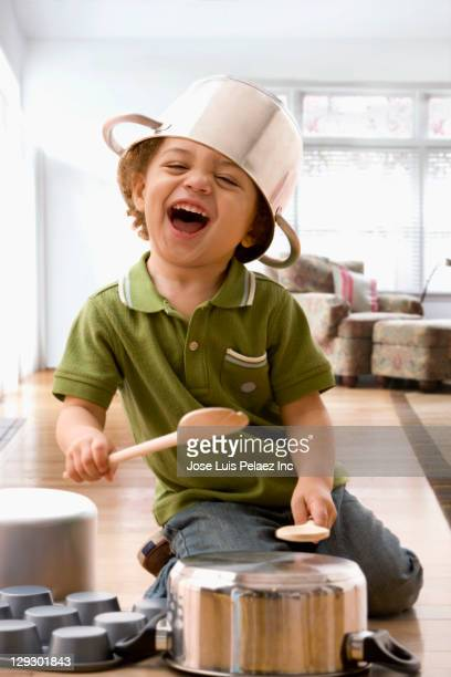 Mixed race boy beating on kitchen pots