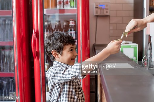 Mixed race boy buying food in restaurant : Stock Photo
