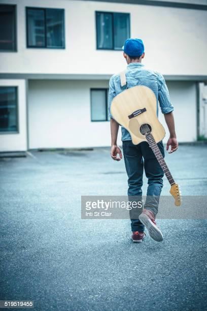 Mixed race boy carrying guitar in parking lot