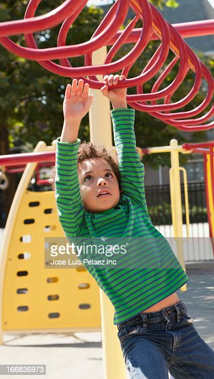 Mixed race boy climbing on jungle gym at playground : Foto de stock