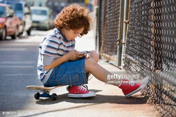 Mixed Race boy dialing cell phone