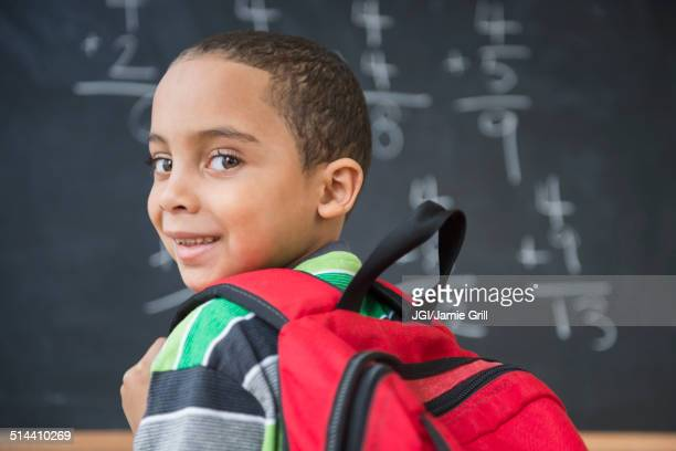 Mixed race boy doing math problems at board in class