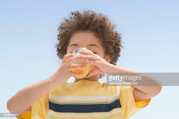 Mixed race boy drinking orange juice