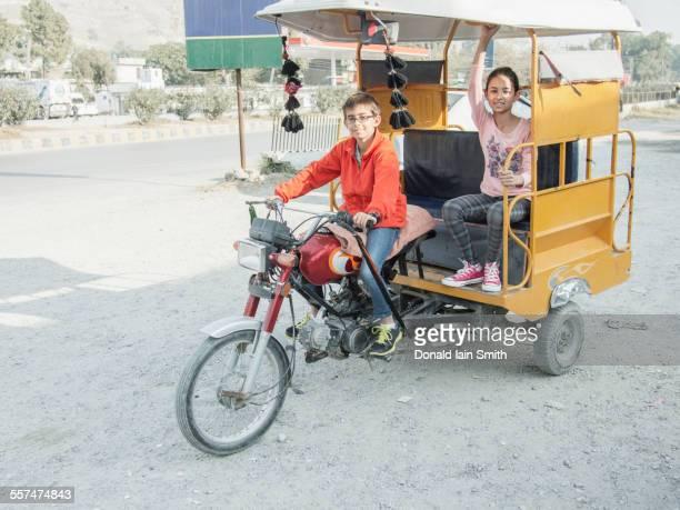 Mixed race boy driving girl in rickshaw