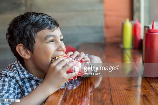 Mixed race boy eating burger in restaurant : Stock Photo