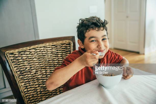Mixed race boy eating cereal at table