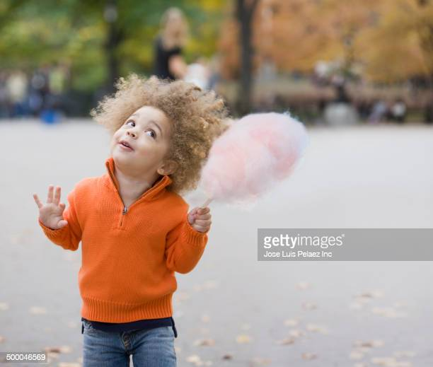 Mixed race boy eating cotton candy in park