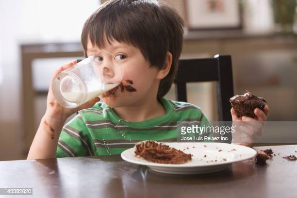 Mixed race boy eating cupcake and drinking milk