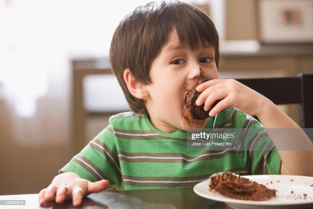 Mixed race boy eating cupcake