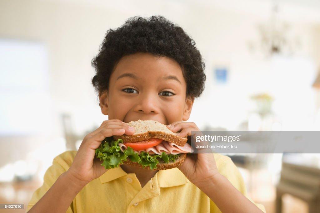 Mixed race boy eating healthy sandwich