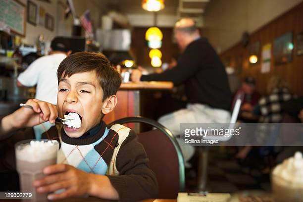 Mixed race boy eating ice cream