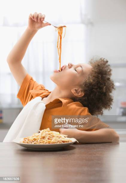 Mixed race boy eating pasta at table