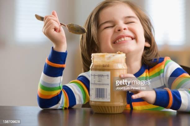 Mixed race boy eating peanut butter
