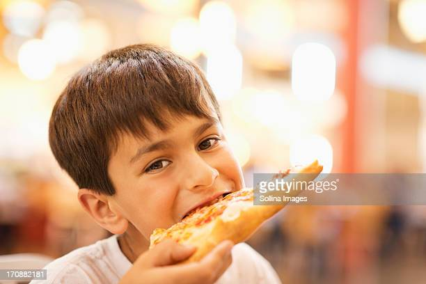 Mixed race boy eating pizza in restaurant