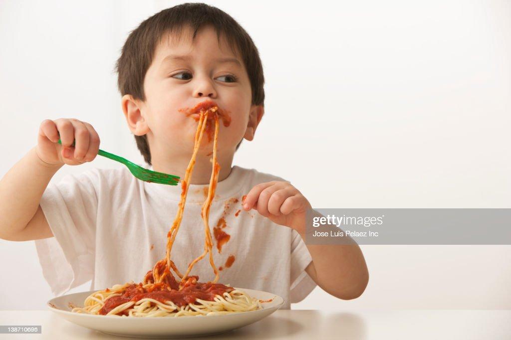 Mixed race boy eating spaghetti : Stock Photo