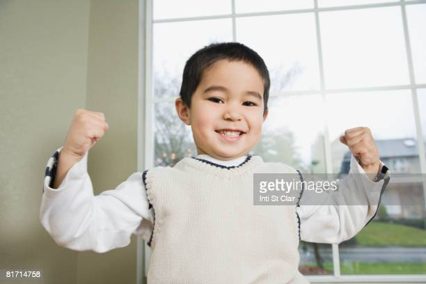 Mixed Race boy flexing muscles