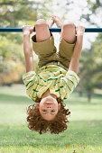 Mixed Race boy hanging upside down