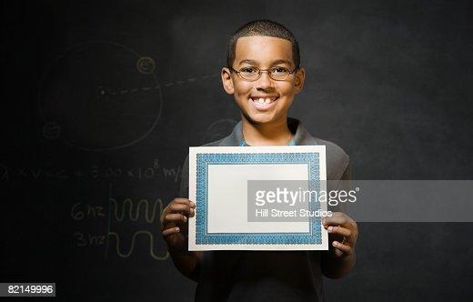 Mixed Race boy holding blank certificate