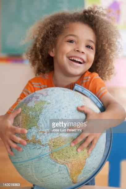 Mixed race boy holding globe