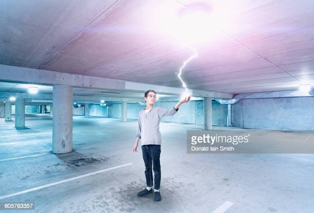 Mixed race boy holding lightning in parking lot