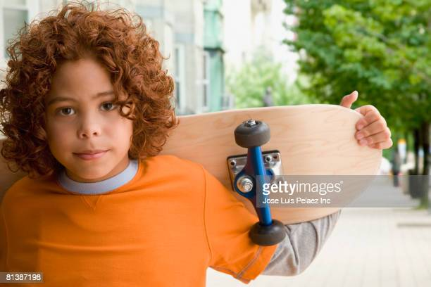 Mixed Race boy holding skateboard