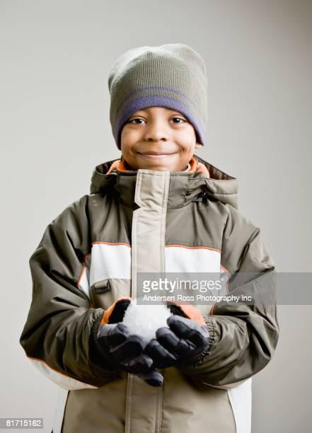 Mixed Race boy holding snowball