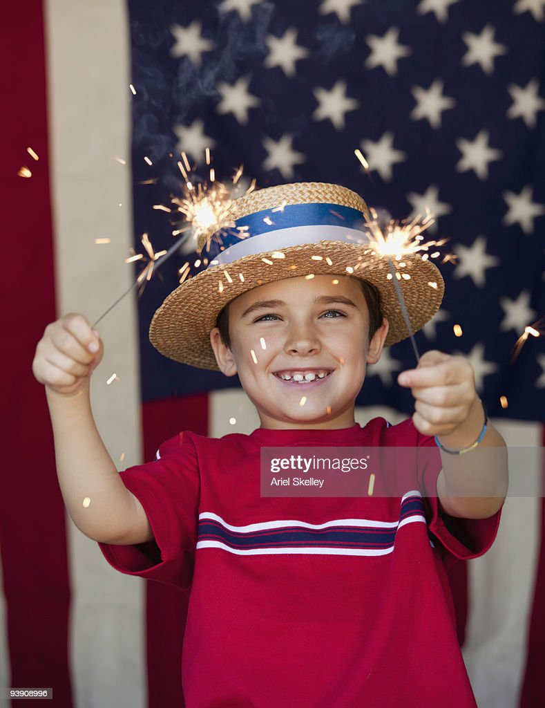 Mixed race boy holding sparklers in front of American flag : Stock Photo
