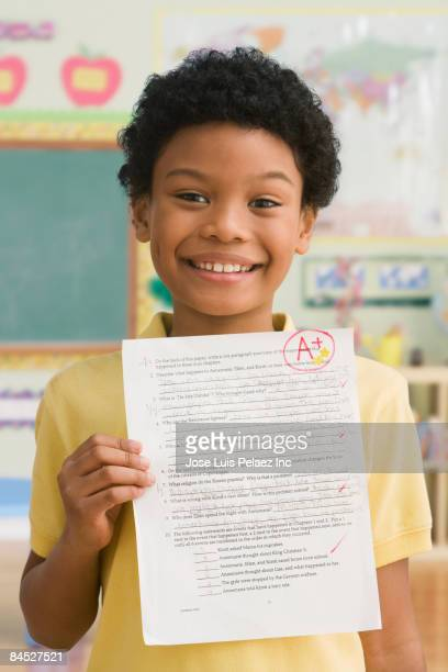 Mixed race boy holding test with A+ in classroom