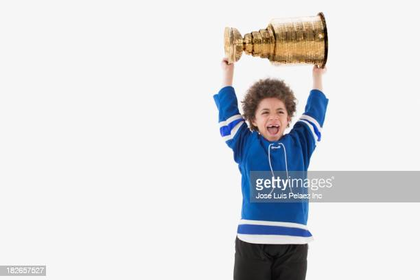 Mixed race boy holding trophy