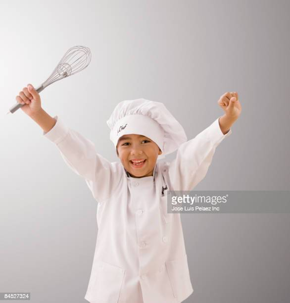 Mixed race boy in chef's whites holding whisk