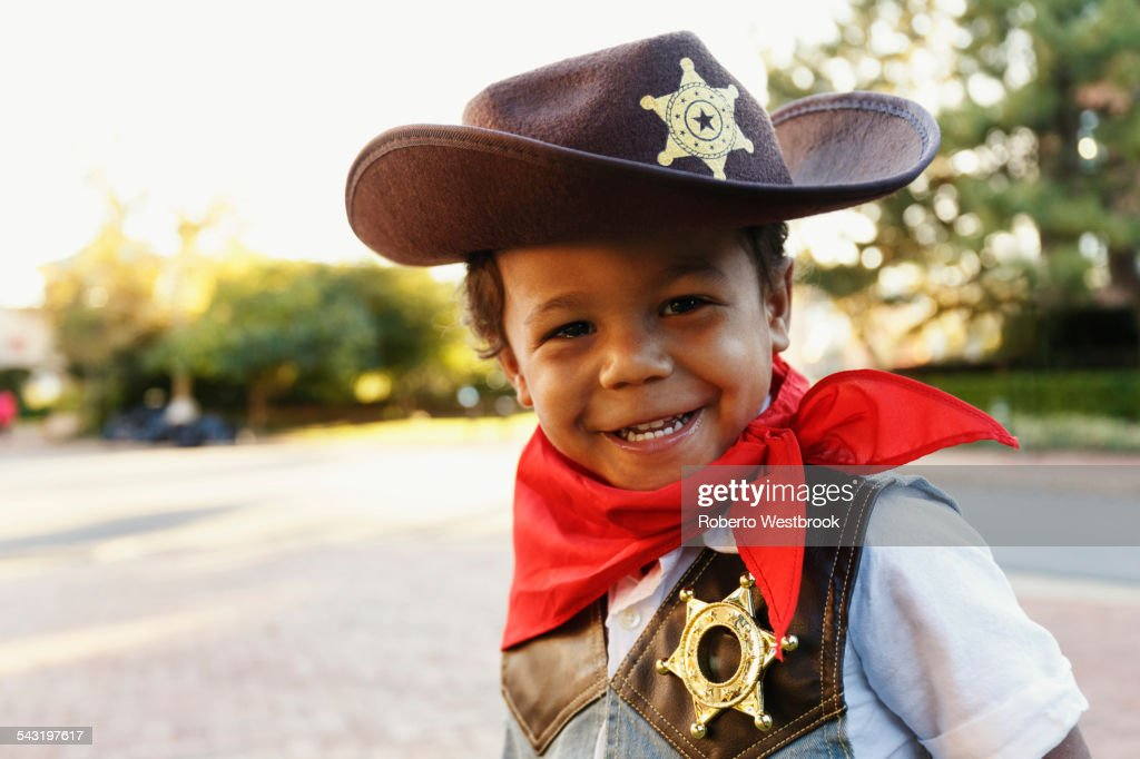 Mixed race boy in cowboy costume smiling outdoors