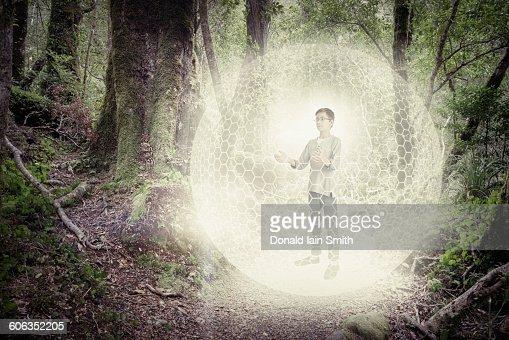 Mixed race boy in digital orb in forest