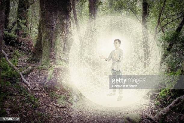 Mixed race boy in digital orb in forest
