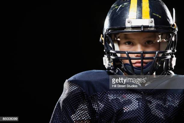 Mixed race boy in football uniform